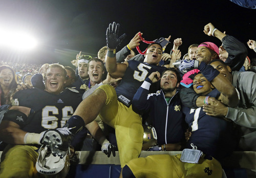In this Sept. 22, 2012 photo, Notre Dame's Chris Watt (66), Manti Te'o (5) and TJ Jones (7) celebrate with fans after Notre Dame defeated Michigan, 13-6,  in an NCAA college football game in South Bend, Ind. Notre Dame defensive coordinator Bob Diaco believes Manti Te'o is the finest football player in college. (AP Photo/Darron Cummings)