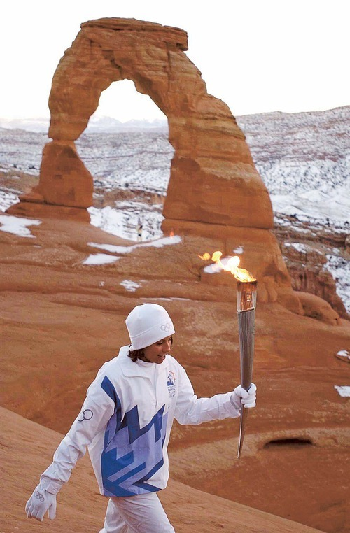 Tribune file photo Stephanie Laree Spann carries the Olympic torch from Delicate Arch in Arches National Park, following a sunrise ceremony and blessing performed by her grandfather.