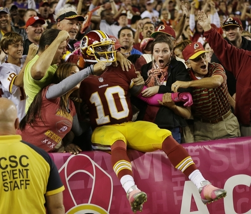 Pablo Martinez Monsivais  |  The Associated Press A still-concussed Robert Griffin III wanders into the FedEx Field stands a futile attempt to find his seat.