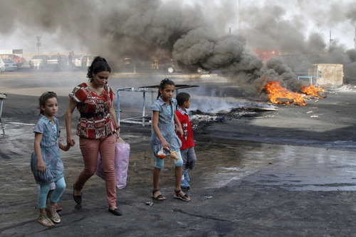 A family walks past flaming tires used as a roadblock to protest the death of Brig. Gen. Wissam al-Hassan, head of the intelligence division of Lebanon's domestic security forces in a car bomb attack targeting his convoy, in the southern port city of Sidon, Lebanon, Saturday, Oct. 20, 2012. Protesters burned tires and set up roadblocks around Lebanon on Saturday in a sign of boiling anger over a massive car bomb that killed a top security official and seven other people a day earlier — a devastating attack that threatened to bring Syria's civil war to Lebanon.(AP Photo/ Mohammed Zaatari)
