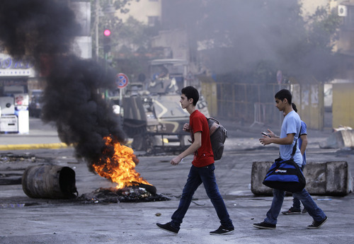 Lebanese students pass by a burning tire laid by Sunni protesters, angry at the killing of Brig. Gen. Wissam al-Hassan, to block a road in Beirut, Lebanon, Saturday, Oct. 20, 2012. A car bomb ripped through Beirut on Friday, killing the top security official and several others, shearing the balconies off apartment buildings and sending bloodied residents staggering into the streets in the most serious blast the Lebanese capital has seen in four years. Dozens of people were wounded in the attack, which the state-run news agency said targeted the convoy of Brig. Gen. al-Hassan. (AP Photo/Hussein Malla)