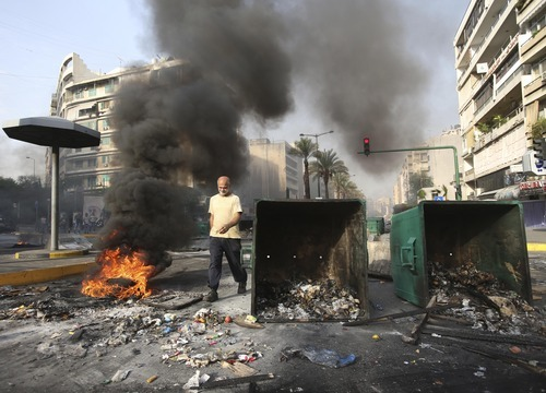 A Lebanese man passes between a burning tire and garbage containers laid by Sunni protesters angry at the killing of Brig. Gen. Wissam al-Hassan, to block a road in Beirut, Lebanon, Saturday, Oct. 20, 2012. A car bomb ripped through Beirut on Friday, killing the top security official and several others, shearing the balconies off apartment buildings and sending bloodied residents staggering into the streets in the most serious blast the Lebanese capital has seen in four years. Dozens of people were wounded in the attack, which the state-run news agency said targeted the convoy of al-Hassan. (AP Photo/Hussein Malla)