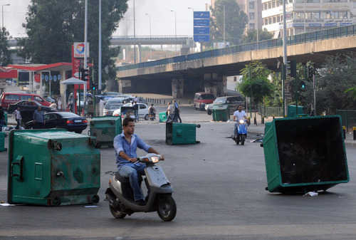 Lebanese citizens ride their motorcycles between garbage containers laid by Sunni protesters, angry at the killing of Brig. Gen. Wissam al-Hassan, to block roads, in Beirut, Lebanon, Saturday, Oct. 20, 2012. A car bomb ripped through Beirut on Friday, killing the top security official and several others, shearing the balconies off apartment buildings and sending bloodied residents staggering into the streets in the most serious blast the Lebanese capital has seen in four years. Dozens of people were wounded in the attack, which the state-run news agency said targeted the convoy of Brig. Gen. al-Hassan. (AP Photo/Ahmad Omar)