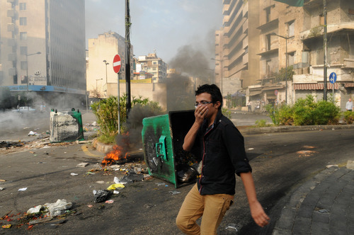 A man covers his mouth as he passes burning garbage containers laid by Sunni protesters, angry at the killing of Brig. Gen. Wissam al-Hassan, to block roads, in Beirut, Lebanon, Saturday, Oct. 20, 2012. Lebanese security officials say angry protesters have closed roads around the country to protest the bombing that killed a top security official and seven other people.(AP Photo/Ahmad Omar)