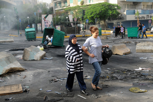 Women walk through a road block of burning garbage containers laid by Sunni protesters angry at the killing of Brig. Gen. Wissam al-Hassan in Beirut, Lebanon, Saturday, Oct. 20, 2012. Lebanese security officials say angry protesters have closed roads around the country to protest the bombing that killed a top security official and seven other people.(AP Photo/Ahmad Omar)