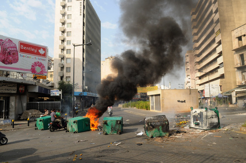 Men on a motorbike navigate burning garbage containers laid by Sunni protesters, angry at the killing of Brig. Gen. Wissam al-Hassan, to block roads, in Beirut, Lebanon, Saturday, Oct. 20, 2012. Lebanese security officials say angry protesters have closed roads around the country to protest the bombing that killed a top security official and seven other people.(AP Photo/Ahmad Omar)