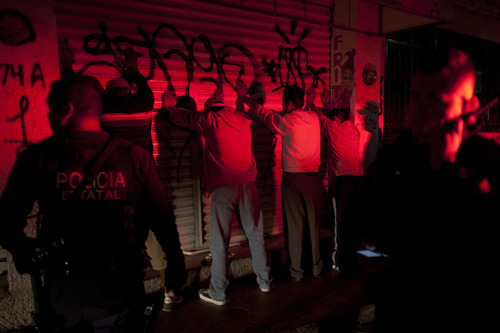 In this Sept. 18, 2012 photo, men stand with their hands on the wall after state police stopped to search them during a routine patrol in Morelia, Mexico. In cities and towns across Mexico, a nearly six-year offensive against drug cartels has been accompanied by a surge in common crime: assaults and robberies that grab no headlines but make life miserable for ordinary citizens.  (AP Photo/Alexandre Meneghini)