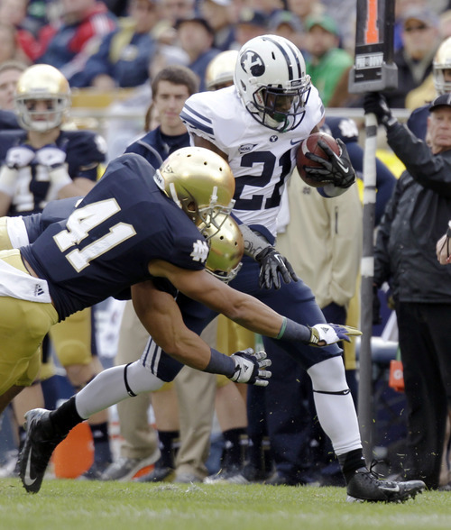 Brigham Young running back Jamaal Williams (21) runs through the tackle of Notre Dame safety Matthias Farley during the first half of an NCAA college football game in South Bend, Ind., Saturday, Oct. 20, 2012. (AP Photo/Michael Conroy)