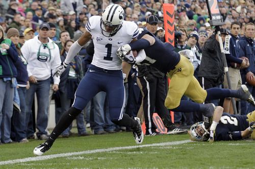 Brigham Young wide receiver Ross Apo (1) is knocked out of bounds at the 2-yard line by Notre Dame safety Zeke Motta during the first half of an NCAA college football game in South Bend, Ind., Saturday, Oct. 20, 2012. (AP Photo/Michael Conroy)