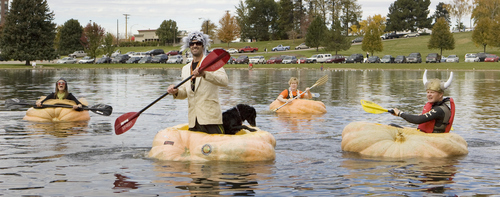 Keith Johnson |  The Salt Lake Tribune Carrie and Kyle Fox, left, Cathy Bradley and Ross Bowman race their giant pumpkins on Sugar House pond during the 2nd annual Ginormous Pumpkin Regatta October 20, 2012 in Salt Lake City. Participants in costume raced giant pumpkins -- some weighing over 1,000 pounds -- across the pond..