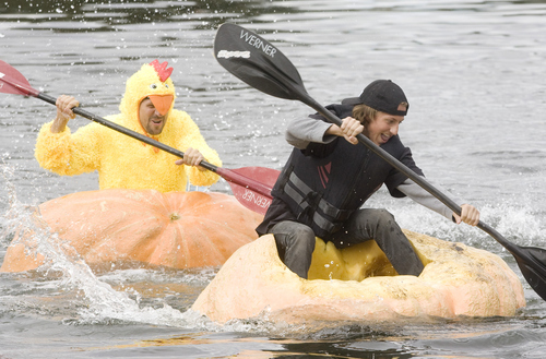 Keith Johnson |  The Salt Lake Tribune Lance Heaton, left, races Indy Heaton across the pond at Sugar  House Park during the 2nd annual Ginormous Pumpkin Regatta October 20, 2012 in Salt Lake City. Some of the pumpkins raced by the costumed participants weighed over 1,000 pounds.