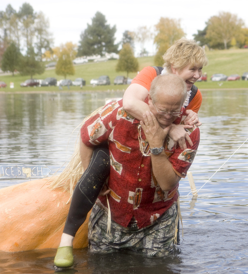Keith Johnson |  The Salt Lake Tribune David Bradley helps his wife, Cathy, out of their giant pumpkin,