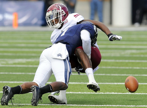 Utah State cornerback Nevin Lawson (blue jersey) separates New Mexico State wide receiver Austin Franklin from the ball during an NCAA college football game on Saturday, Oct. 20, 2012, in Logan, Utah. (AP Photo/The Herald Journal, Eli Lucero)