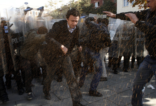 Opposition party leader Albin Kurti, left, runs through pepper spray used by Kosovo police to disperse a crowd of anti-Serbia protesters in Kosovo's capital Pristina, Monday, Oct. 22, 2012. Kosovo police in riot gear fired tear gas and used batons to disperse dozens of ethnic Albanians protesting a meeting between Prime Minister Hashim Thaci and Serbian leader Ivica Dacic. The protest early Monday was called by Self-Determination, a hardline opposition group that opposes any talks with Serbia. (AP Photo/Visar Kryeziu)
