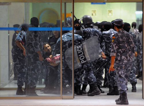 Kuwait riot policemen arrest a man during a demonstration in Kuwait City in the early hours of Monday, October 22, 2012. Several thousand protestors from opposition groups, local tribes and former MPs gathered in different points of Kuwait City to demonstrate against the Government's amendment of the country electoral law.(AP Photo/Gustavo Ferrari)