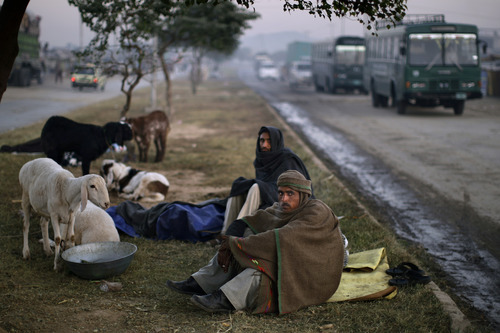 Pakistani Saleem Akhtar, 28, foreground, and Azmat Sadiq, 29, wrap themselves with shawls to contend with the early morning cold, while waiting for customers to buy their sheep for the upcoming Muslim holiday of Eid al-Adha, or