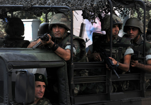 Lebanese Army soldiers patrol a neighborhood after overnight clashes between Sunni and Shiite gunmen in Beirut, Lebanon, Monday, Oct. 22, 2012. Shortly before noon Lebanese troops began a big operation in the capital aiming to open all closed roads and to force gunmen out of the streets after overnight clashes between Sunni and Shiite gunmen following the funeral of Lebanese Brig. Gen. Wissam al-Hassan, who was killed in a car bomb in an east Beirut neighborhood on Friday. (AP Photo/Ahmad Omar)