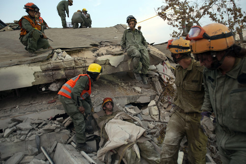 Israeli soldiers from the Home Front Command attend to a soldier acting as a survivor in the rubble of a school during a drill simulating an earthquake in Holon, Israel, Sunday, Oct. 21, 2012. Israel began a five-day civil defense drill, code-named Turning Point 6 on Sunday, putting soldiers, emergency crews and civilians through rehearsals for the possibility of an earthquake and a Tsunami. (AP Photo/Ariel Schalit)
