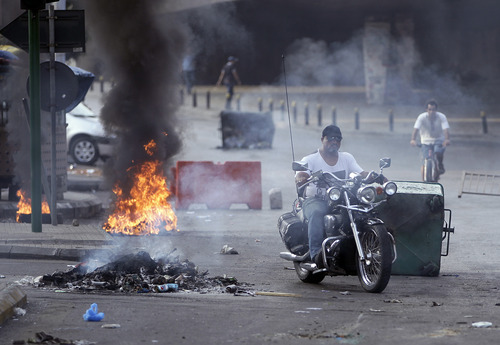 A Lebanese man rides his motorcycle between a burning tire and garbage containers laid by Sunni protesters after overnight clashes between Sunni and Shiite gunmen in Beirut, Lebanon, Monday Oct. 22, 2012. Lebanese security officials say overnight clashes in Beirut between Sunni and Shiite gunmen have wounded several people. The officials say troops managed to separate the gunmen and calm returned Monday morning to the two neighborhoods in the capital where fighting had erupted.(AP Photo/Hussein Malla)