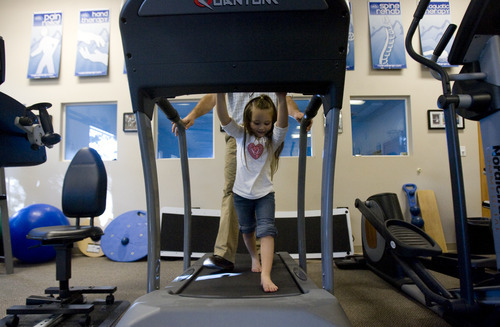 Kim Raff | The Salt Lake Tribune Kiarah McCoy walks on a treadmill with her physical therapist Josh Brown following surgery to rebuild her hip at Rock Run Physical Therapy & Rehab Specialists in Roy, Utah on October 10, 2012. The 4-year-old's hip dysplasia might have been easily fixed had it been caught earlier by her pediatrician. The last surgery, her third, is her mother Sarah McCoy's last hope for her daughter to regain mobility. But the family, though fully insured, is struggling to pay their medical bills.