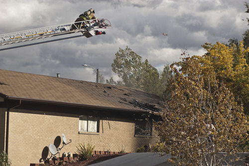 Donald W. Meyers | The Salt Lake Tribune A Payson firefighter surveys the roof damage from an apartment building fire Monday moring. Fire officials are still investigating the cause of the blaze, which spread to multiple apartments.