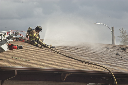 Donald W. Meyers | The Salt Lake Tribune A Payson firefighter sprays water through the roof of an apartment building Monday morning. Fire officials are still investigating the cause of the blaze, which spread to multiple apartments.