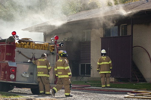 Donald W. Meyers | The Salt Lake Tribune Payson and Salem firefighters enter a burning apartment building Monday morning. Payson fire officials are still investigating the cause of the blaze, which spread to multiple apartments.