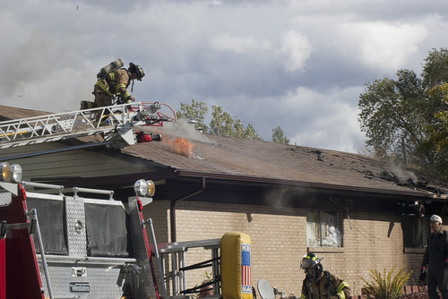 Donald W. Meyers | The Salt Lake Tribune A Payson firefighter reacts to fire coming through the roof of a Payson apartment building Monday morning. Payson fire officials are still investigating the cause of the blaze, which spread to multiple apartments.