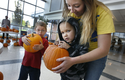 Scott Sommerdorf  |  The Salt Lake Tribune               Ty Hudson, 7, center, holds his pumpkin with the help of his teacher, Shaunie Bills, as Benjamin Peterson, 6, left gets a grip on his choice. Children at the Kauri Sue Hamilton School in Riverton got a special Halloween delivery from an unlikely source. More than 3,500 pumpkins harvested, gathered, and cleaned by Utah State Prison inmates in the Utah State Prison's Greenhouse program were donated to various organizations that serve children in our community.
