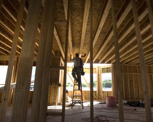 Paul Fraughton | Salt Lake Tribune A plumber works on a new home in an Ivory Homes development in Draper.   Wednesday, October 10, 2012