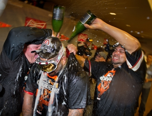 San Francisco Giants' Pablo Sandoval, center, is doused by pitcher Jose Mijares, right, in the clubhouse following Game 7 of baseball's National League championship series against the St. Louis Cardinals, Monday, Oct. 22, 2012, in San Francisco. The Giants won 9-0. (AP Photo/The Sacramento Bee, Randy Pench)
