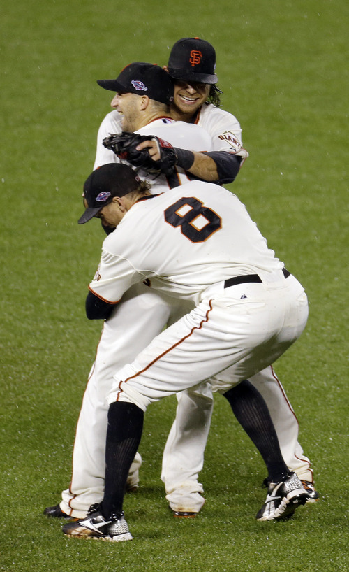 San Francisco Giants' Marco Scutaro, Hunter Pence (8) and Brandon Crawford celebrate after the final out in Game 7 of baseball's National League championship series against the St. Louis Cardinals Monday, Oct. 22, 2012, in San Francisco. The Giants won 9-0 to win the series. (AP Photo/Eric Risberg)