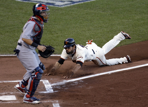 San Francisco Giants' Angel Pagan scores past St. Louis Cardinals catcher Yadier Molina during the first inning of Game 7 of baseball's National League championship series Monday, Oct. 22, 2012, in San Francisco. (AP Photo/Eric Risberg)