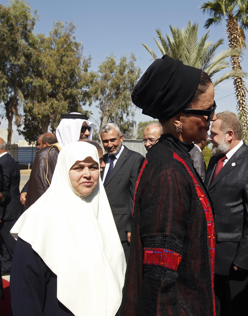 Qatar's First Lady Sheika Mozah bint Nasser al-Missned, right, and her Gazan counterpart, left, attend a welcome ceremony upon her arrival at the Rafah border crossing with Egypt, southern Gaza Strip, Tuesday, Oct. 23, 2012. The emir of Qatar is visiting the Gaza Strip, the first head of state to visit the Palestinian territory since Islamist Hamas militants seized control there five years ago and will deliver more than $250 million in aid, a move that will bolster Hamas and ease its international isolation. (AP Photo/ Mohammed Abed, Pool)