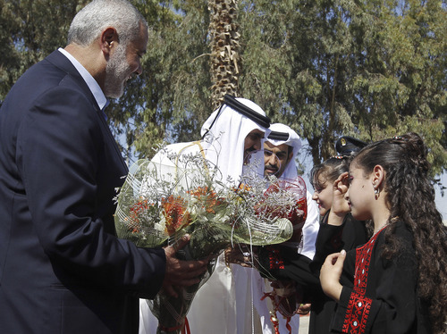 Gaza's Hamas Prime Minister Ismail Haniyeh, left, and Emir of Qatar Sheikh Hamad bin Khalifa al-Thani, second left, receive flowers from Palestinian girls during a welcome ceremony in Rafah, southern Gaza Strip, Tuesday, Oct. 23, 2012. The emir of Qatar received a hero's welcome in Gaza on Tuesday, the first head of state to visit the Palestinian territory since Islamist Hamas militants seized control there five years ago. He will deliver more than $250 million in aid, a move that will bolster Hamas and ease its international isolation. (AP Photo/ Mohammed Abed, Pool)