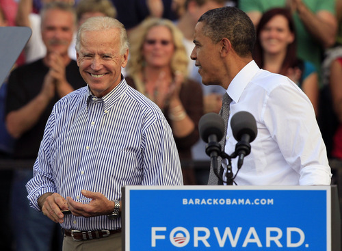 President Barack Obama takes the podium after being introduced by Vice President Joe Biden, left, at a joint campaign rally, Tuesday, Oct. 23, 2012, at Triangle Park in Dayton, Ohio. (AP Photo/Al Behrman)