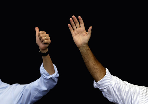 The arms of Republican presidential candidate, former Massachusetts Gov. Mitt Romney, right, and his vice presidential running mate, Rep. Paul Ryan, R-Wis., gesture as the crowd cheers at a campaign event Tuesday, Oct. 23, 2012, in Henderson, Nev. It was the first joint appearance after Monday's last presidential debate between Romney and President Barack Obama. (AP Photo/David Goldman)