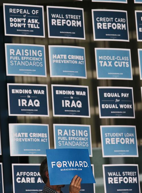 A member of a crowd of area supporters holds a sign while standing in front campaign posters during a visit by Vice President Joe Biden at the J. Babe Stearn Community Center on Monday, Oct. 22, 2012, in Canton, Ohio. (AP Photo/Akron Beacon Journal, Ed Suba Jr.) MANDATORY CREDIT