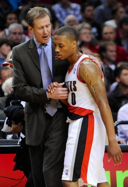 Portland Trail Blazers' head coach Terry Stotts speaks with Damian Lillard during the second half of an NBA preseason basketball game in Portland, Ore., Monday, Oct., 22, 2012. (AP Photo/Greg Wahl-Stephens)