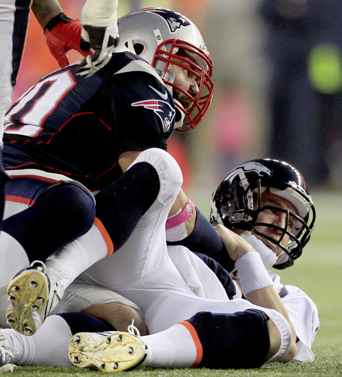 Denver Broncos quarterback Peyton Manning, right, watches his fumble after being sacked by New England Patriots defensive end Rob Ninkovich (50) in the third quarter of an NFL football game, Sunday, Oct. 7, 2012, in Foxborough, Mass. (AP Photo/Steven Senne)