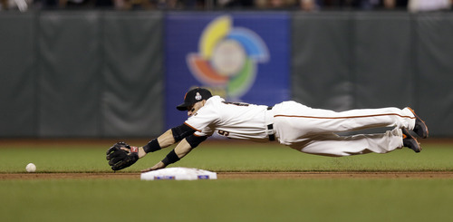 San Francisco Giants' Marco Scutaro dives for a single by Detroit Tigers' Delmon Young during the sixth inning of Game 1 of baseball's World Series Wednesday, Oct. 24, 2012, in San Francisco. (AP Photo/Marcio Jose Sanchez)