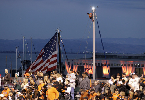 A fan watches from the mast of a boat during the fourth inning of Game 1 of baseball's World Series between the San Francisco Giants and the Detroit Tigers Wednesday, Oct. 24, 2012, in San Francisco. (AP Photo/Eric Risberg)