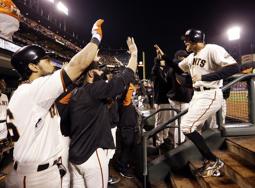San Francisco Giants' Hunter Pence is congratulated in the dugout after scoring during the seventh inning of Game 2 of baseball's World Series against the Detroit Tigers Thursday, Oct. 25, 2012, in San Francisco. (AP Photo/David J. Phillip)