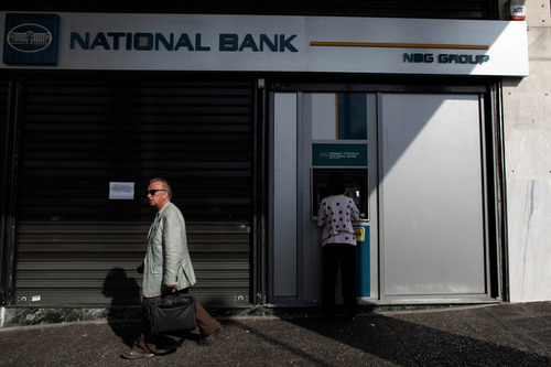 A woman uses an ATM machine outside a closed branch of National Bank of Greece, during a 48-hour bank employee strike over austerity measures, in central Athens, on Thursday, Oct. 25, 2012. Greece's Finance Minister said the country has been granted a long-sought extension to meet the terms of its bailout program — but the claim was swiftly shot down as