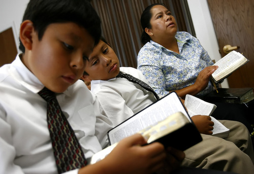 Tribune file photo  L-R Jesus Saavedra, 9, Christopher Saavedra, 7, and Gloria Saavedra read along in the bible during a scripture reading during Spanish-speaking LDS service for children at Stake Center at 3900 S. 4000 West in 2006.
