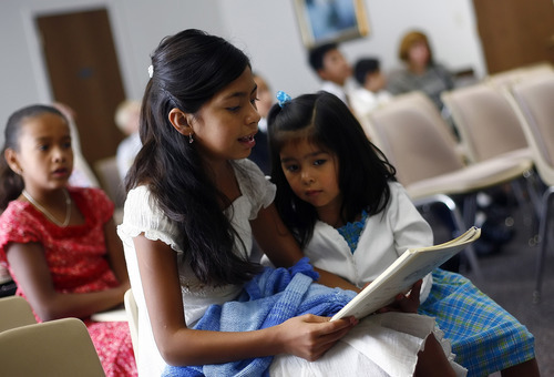 Tribune file photo  Nicole Rivas, 10, left, and Nadia Rivas, 3, sing songs during the Spanish-speaking LDS service for children at Stake Center at 3900 S. 4000 West in 2006.