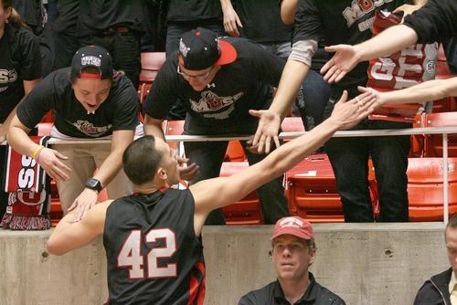 Paul Fraughton | The Salt Lake Tribune.  Jason Washburn high fives fans in the student section after the Ute's overtime win against Washington State. Utah played Washington State in the Huntsman Center.  Thursday, January 5, 2012
