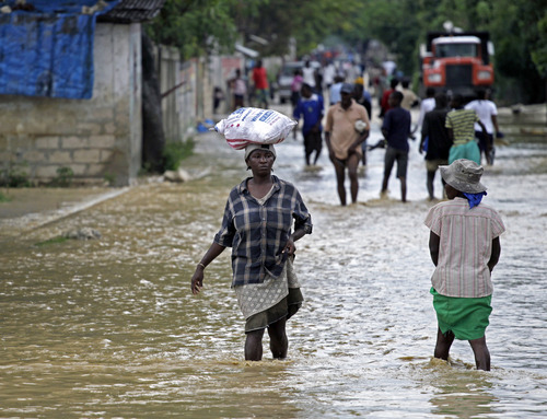 Locals walk across the flooded streets of La Plaine, Haiti, Thursday, Oct. 25, 2012, after Hurricane Sandy caused flooding and claimed three lives. Hurricane Sandy roared across Cuba overnight, making landfall as a powerful 115-mph storm. Haiti's capital, Port-au-Prince is still feeling the ripple effects, with gusty continuing rain as the Sandy makes its way towards the Bahamas. (AP Photo/The Miami Herald, Carl Juste)  MAGS OUT