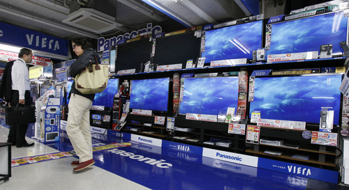 People inspect flat-panel TVs at a discount store in Tokyo Friday, Oct. 26, 2012. Japan's Cabinet approved a 423 billion yen ($5.3 billion) economic stimulus package on Friday, moving to fend off recession amid signs the recovery in the world's third biggest economy is faltering. The decision coincided with news of a 0.1 percent fall in the consumer price index in September, adding to pressure on the central bank to ease policies to help fight deflation, or falling prices, which can hinder economic growth. (AP Photo/Koji Sasahara)