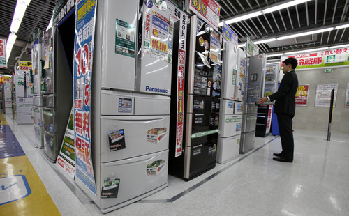 A man inspects a refrigerator at a discount electric store in Tokyo Friday, Oct. 26, 2012. Japan's Cabinet approved a 423 billion yen ($5.3 billion) economic stimulus package on Friday, moving to fend off recession amid signs the recovery in the world's third biggest economy is faltering. The decision coincided with news of a 0.1 percent fall in the consumer price index in September, adding to pressure on the central bank to ease policies to help fight deflation, or falling prices, which can hinder economic growth. (AP Photo/Koji Sasahara)